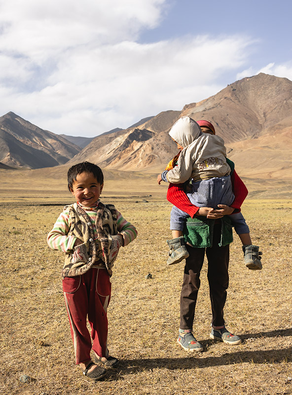 Three nomadic children from a yurt camp in the Pshart Valley playing and smiling
