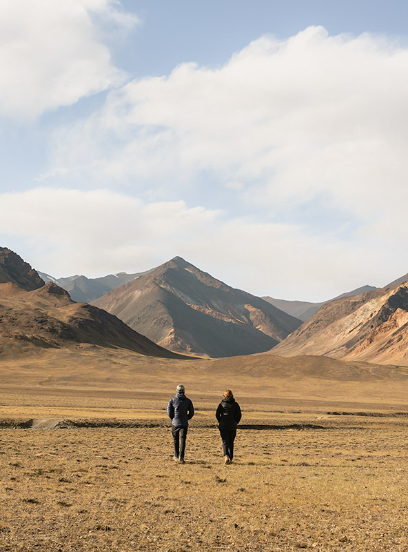 A man and woman walking towards mountains in the Pshart Valley