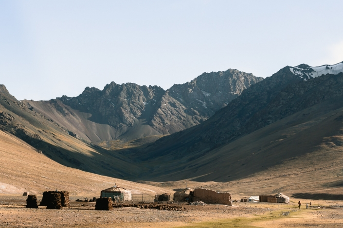 A yurt camp at the foot of the Gumbezkol Valley, set against the backdrop of the Pshart Range's jagged peaks in Eastern Tajikistan.
