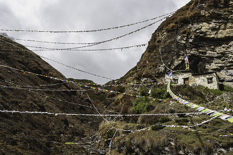 Monastery buildings clinging to a steep grassy hillside with colourful prayer flags strung all around
