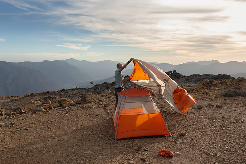 Putting up the tent with the aid of a gust of wind, the fly billowing out like a sail. Above Wadi Bih in the mountains of Musandam, this is one of the most special campsites in Oman.
