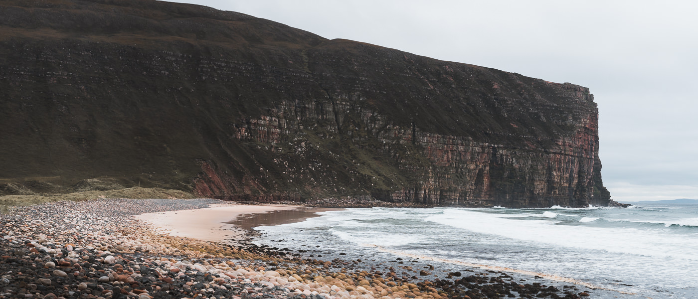 The sandy beach at Rackwick Bay on Hoy, bordered by large rounded stones and backed by towering and rugged cliffs
