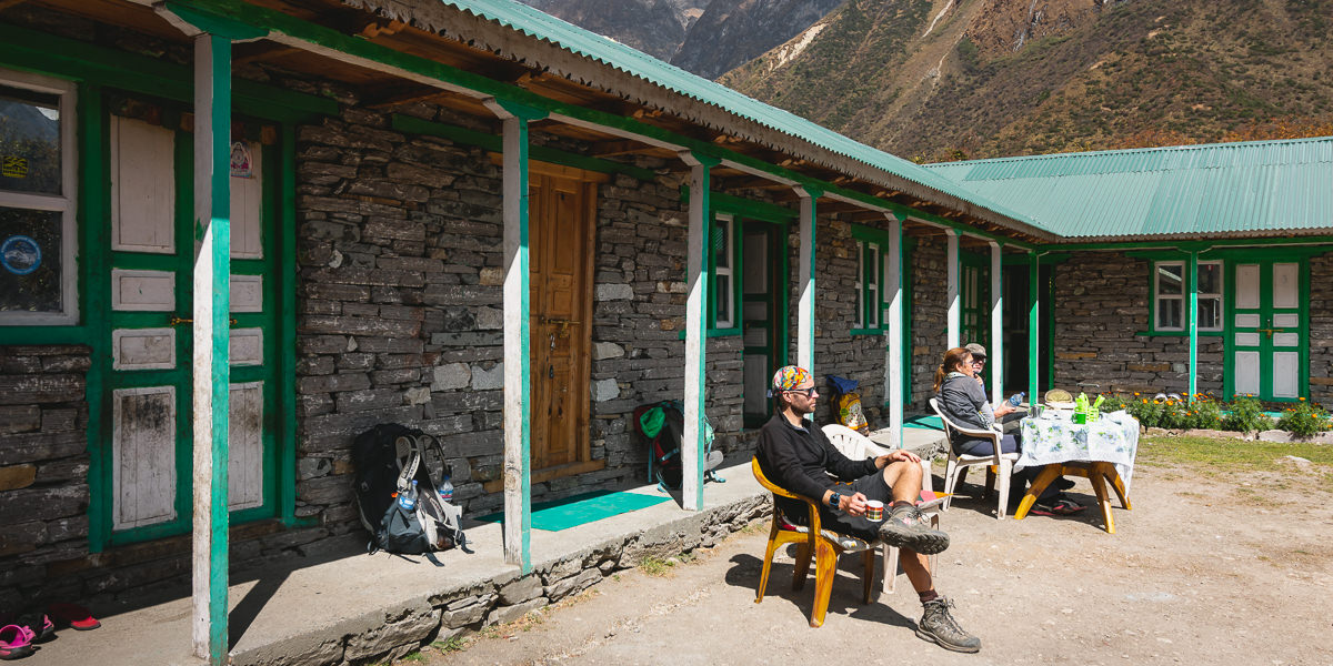 Trekkers sitting in a sunny guesthouse courtyard in Samagaun on the Manaslu Circuit