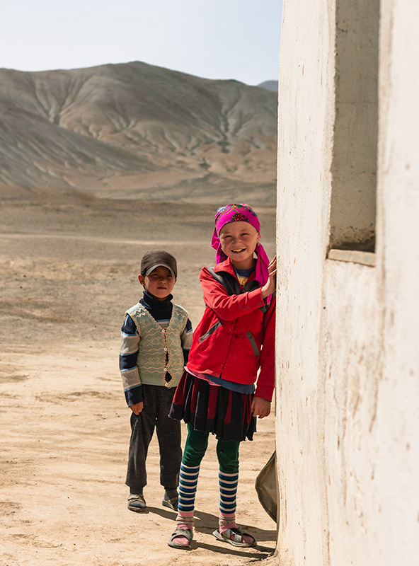 A smiling girl and her yournger brother peering out from behind a wall in Rangkul Village, Tajikistan