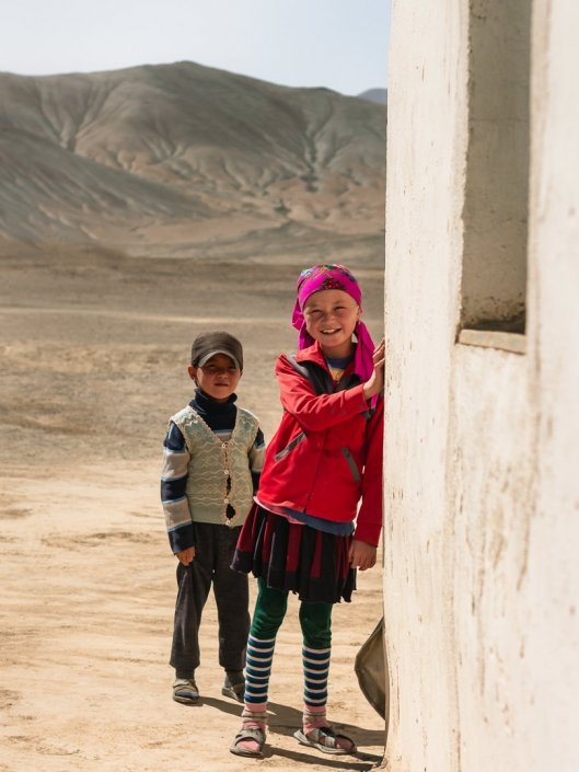 A girl in a red jacket smiles in the dusty surroundings of Rangkul Village in the Eastern Pamirs of Tajikistan.
