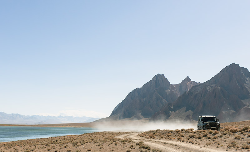 A black Landcruiser and trail of dust behind it, driving by Rangkul Lake off the Pamir Highway