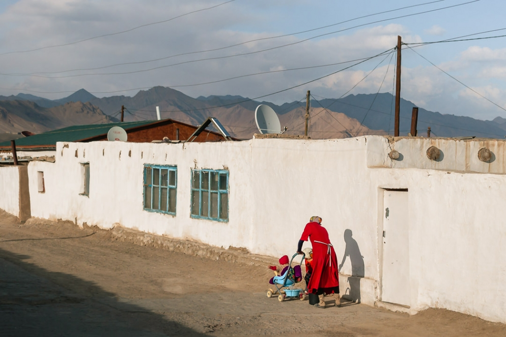 A local woman in a bright red outfit makes her way through the whtewashed streets of Murghab with her two children.