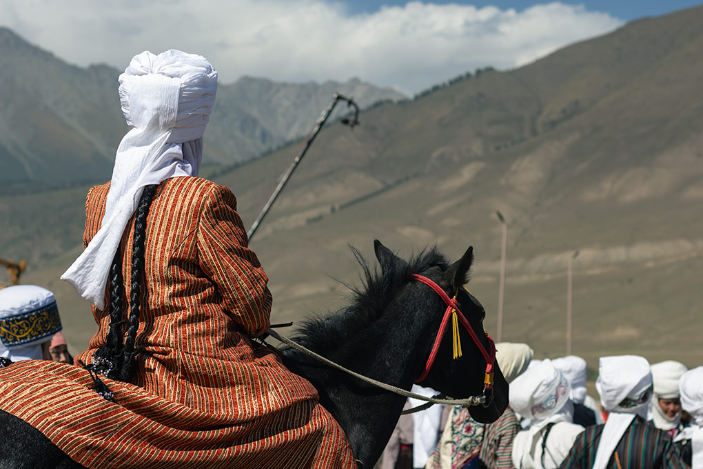 Sitting regally on her black horse, this woman takes the prize for the best coat at the World Nomad Games in Kyrgyzstan. The orange and gold vertical stripes pf her long coat glint in the sun and her long braided black hair hangs below her flowing white headdress.