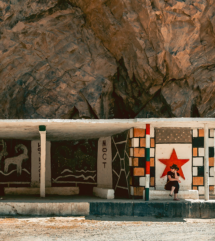 A tourist sitting at a colourful Soviet era bus stop along the Pamir Highway