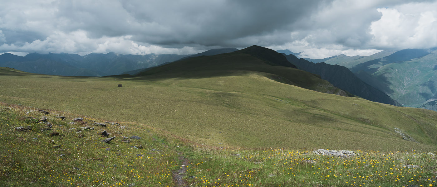 The trail leads onto the ridgetop meadow, past the old stone shelter, and on towards Mt Pitsilamta (seen here under heavy clouds), on Day 1 of the Tusheti to Pankisi trek