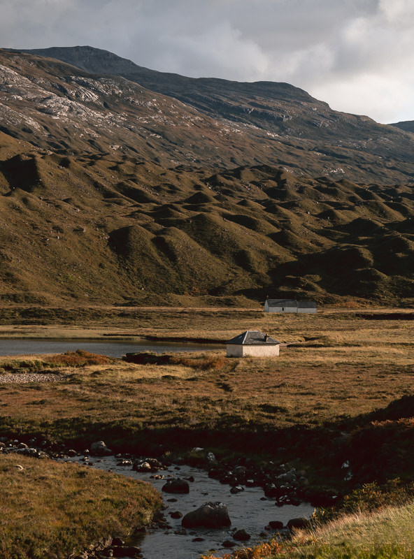 Cottages in the afternoon sun next to the River Torridon on Scotland's North Coast 500.