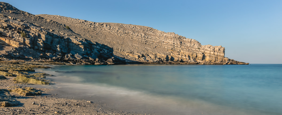 Rocky Beach in Musandam, turquoise water lapping a pebble beach surrounded by golden limestone cliffs