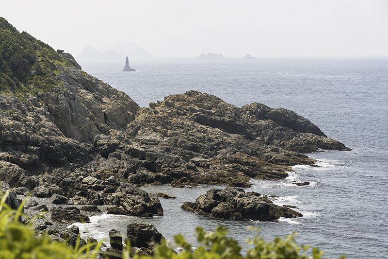 Rocky coast on southeast Hachuja-do on a hazy afternoon on Jeju Olle Trail Route 18-1
