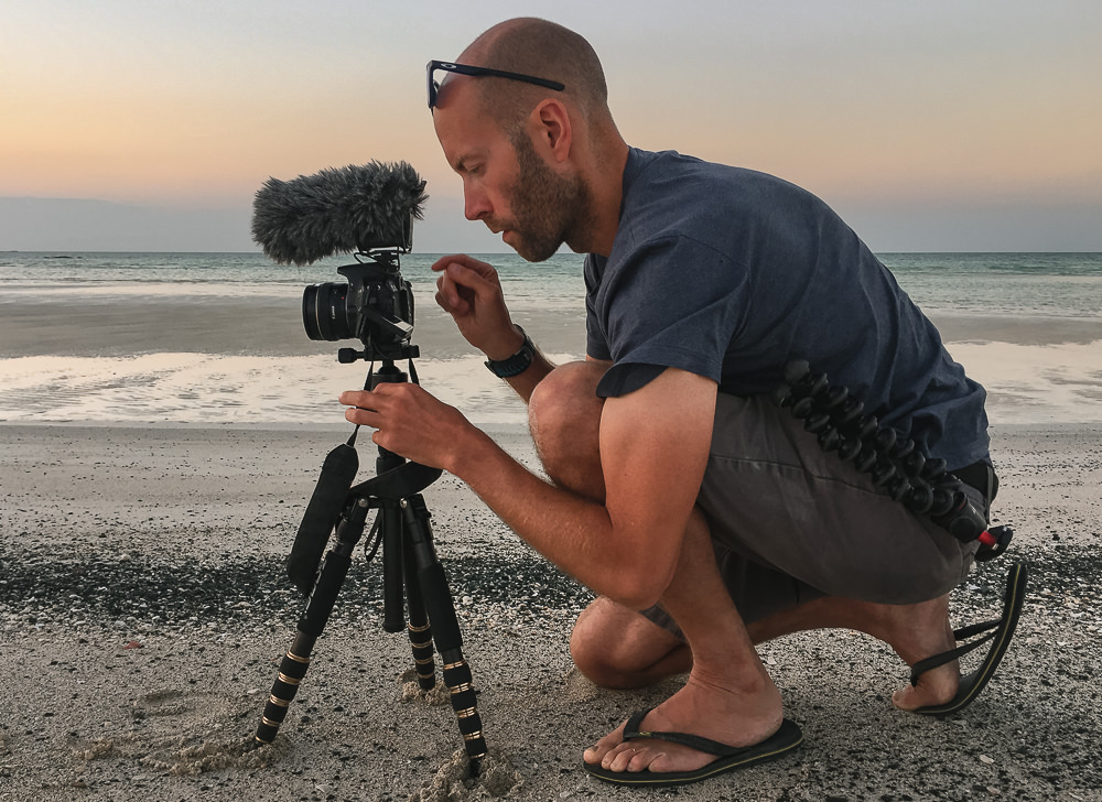 A person crouched in front of a tripod on a sand beach on Masirah Island, capturing the sound of the waves with the Rode Video Mic Pro, an indispensible part of the travel photography gear setup