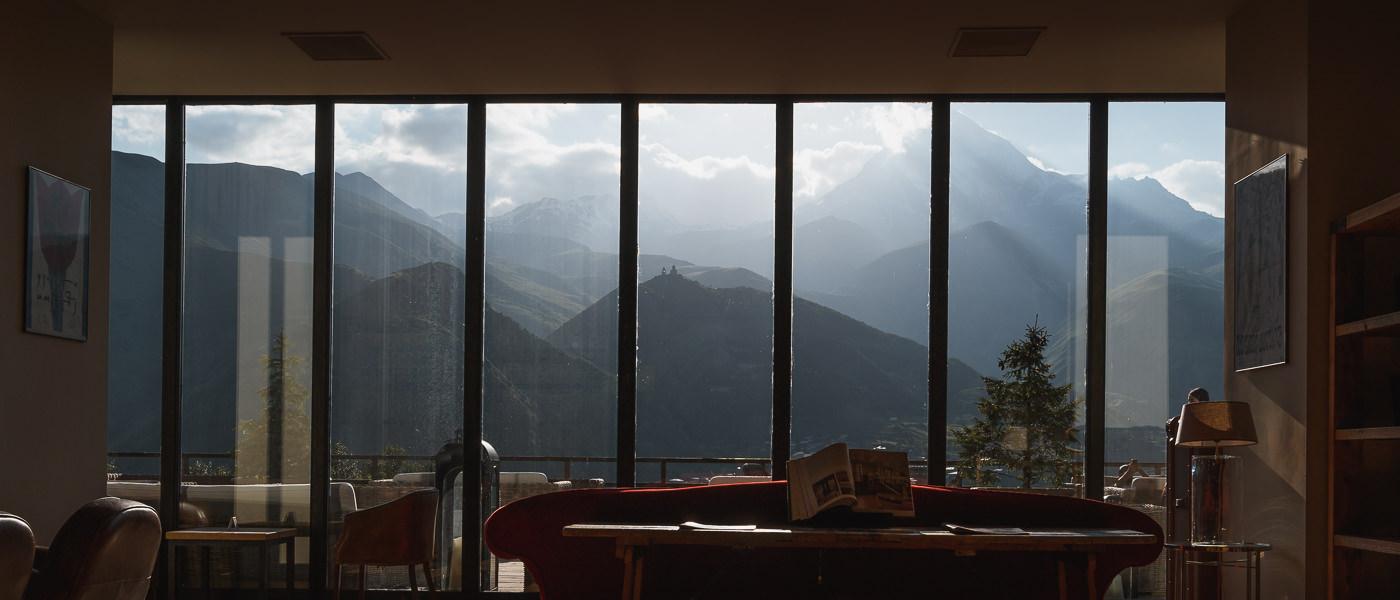 A view of Mount Kazbek and Gergeti Holy Trinity Church, seen through the window at luxury hotel Rooms Kazbegi