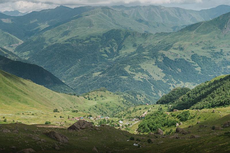 The village of Roshka, nestled in the green, sunlit Roshka Valley at the end of the Juta to Roshka hike in Georgia