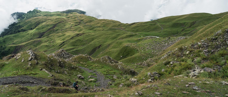 A hiker descends the winding trail to Sakisto Lake on day 5 of the Tusheti Pankisi trek