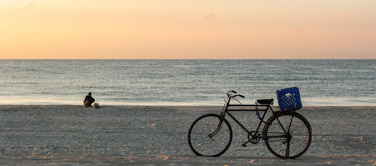 A bicycle and fisherman on Salalah Beach at sunrise