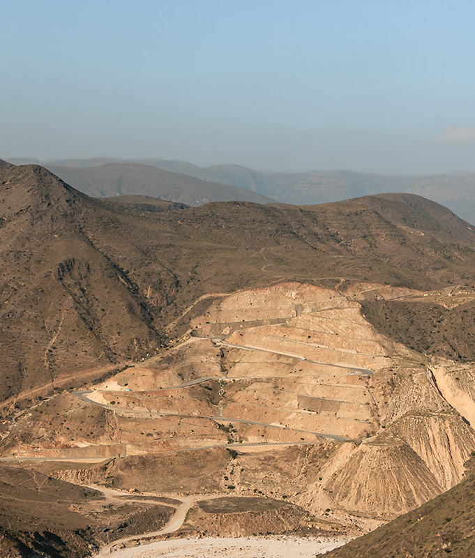 A winding road cut into the dusty mountainside west of Salalah