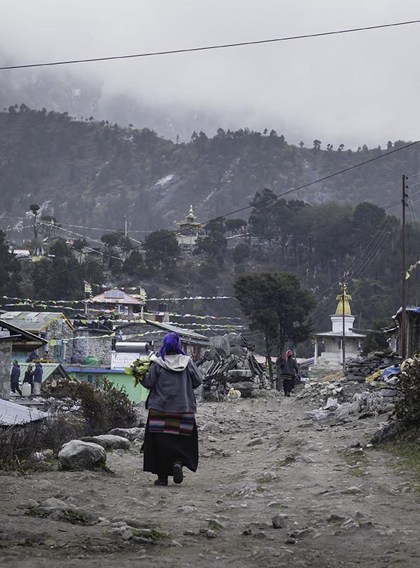 A woman walks along the rough main street of Samagaun under grey skies
