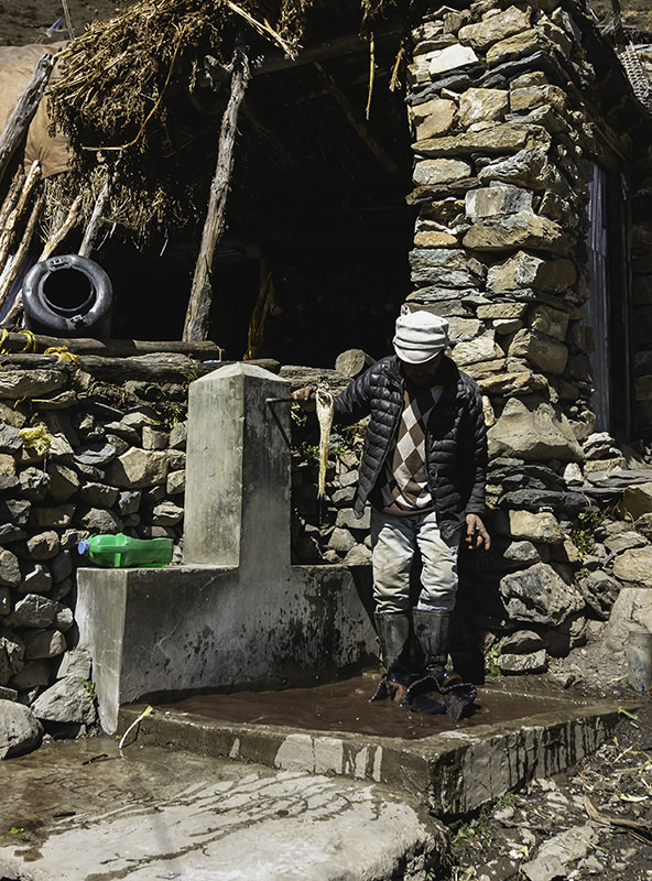 A man cleaning a rug by foot in a stone bath outside in Samdo, a village on the Manaslu Circuit Trek