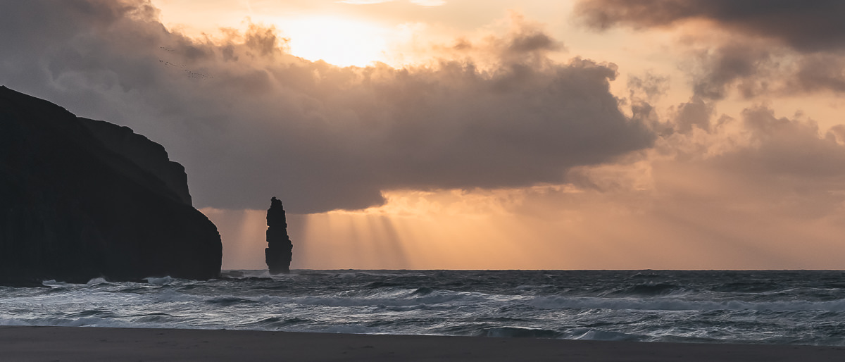 Am Buachaille seat stack silhouetted against the setting sun at Sandwood Bay, one of the best North Coast 500 side trips