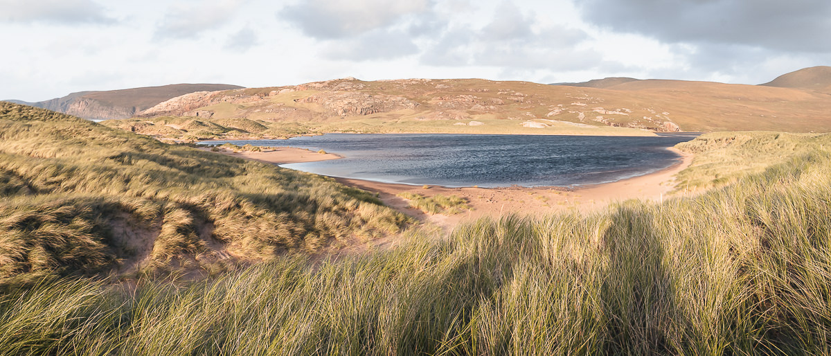 A wind whipped Sandwood Loch surrounded by machair covered dunes basking in the afternoon sun