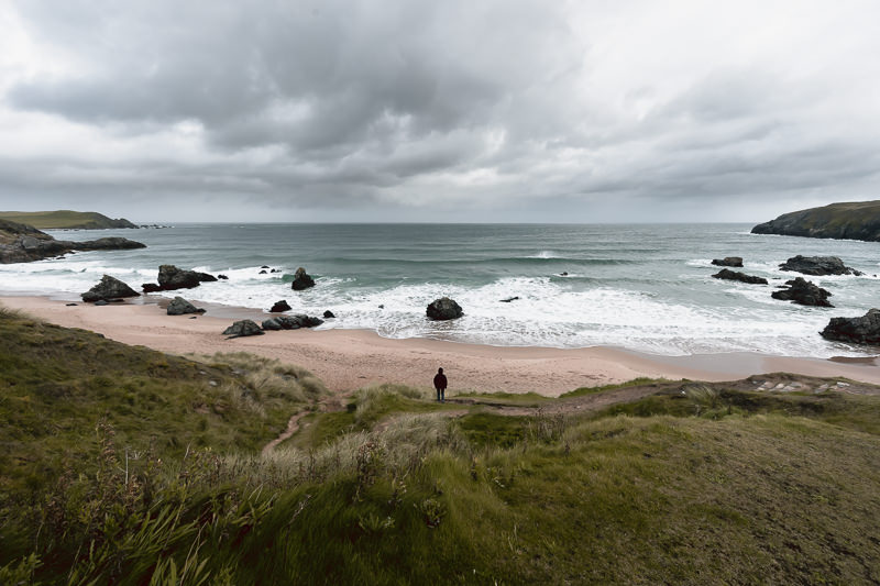 A person stands looking out at the sea past the huge rocks on Sango Sands, one of Scotland's most northerly beaches and a popular place to visit on the North Coast 500 route.
