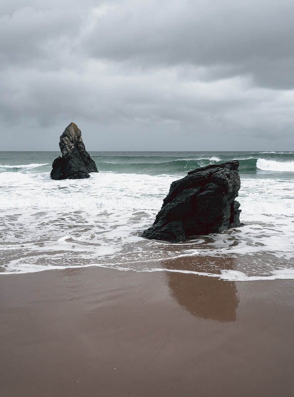 Two large black rocks embedded in the sand on the shoreline at Sango Sands in northwest Scotland.