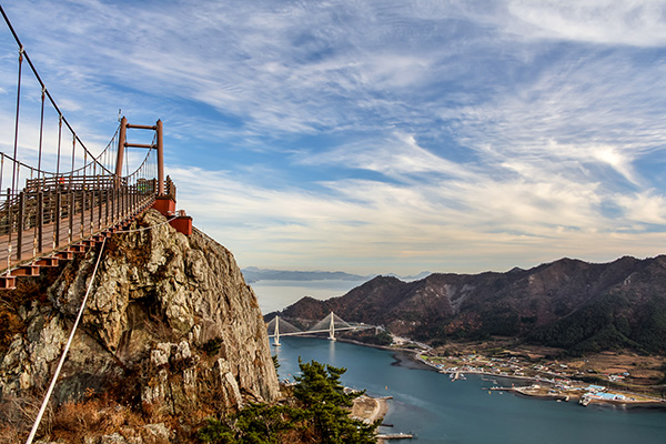 Looking towards one of Saryangdo Island's suspension bridges from the ridge hiking trail, with the road bridge and surrounding islands in the distance, South Korea