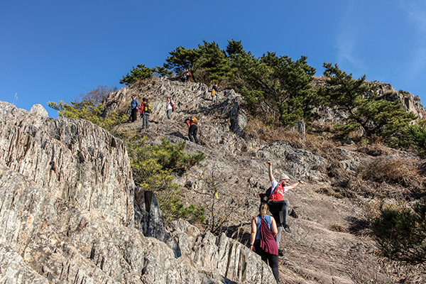 Climbing a steep rock face on Saryangdo Island Ridge Hike, Tongyeong, South Korea