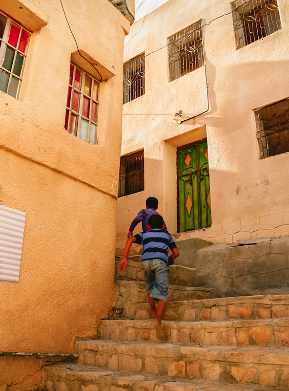 Two kids running up stone steps in a narrow street in one of the villages on the Sayq Plateau in Oman