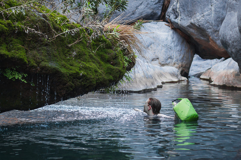 The Scrubba Washbag, used here by a person in the water, is a multi purpose item for a backpacking camping gear setup