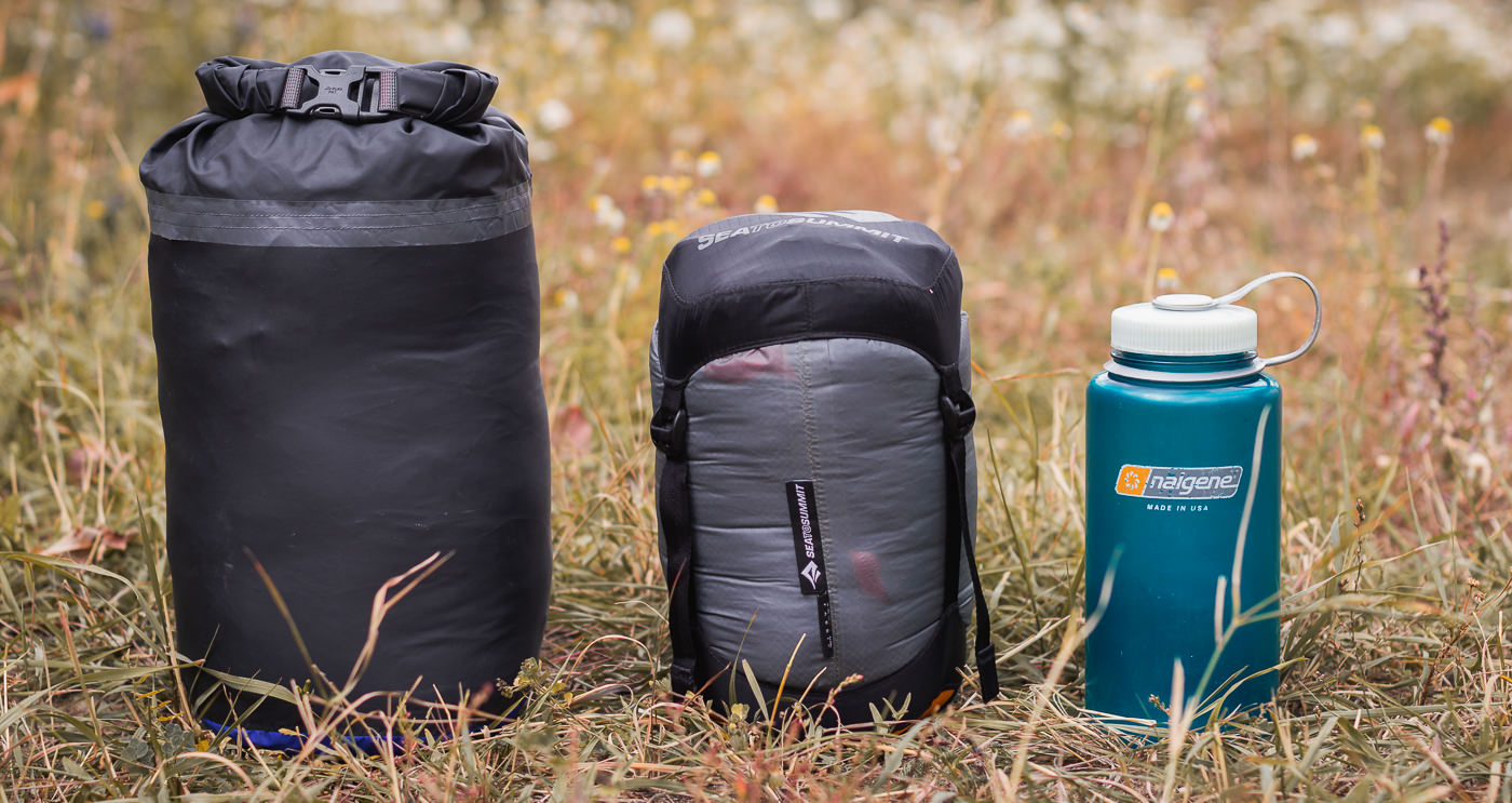 A Sea to Summit compression sack compared against the original Rab sleeping bag stuff sack and a Nalgene water bottle, showing that it's a useful addition to any backpacking camping gear setup by packing a sleeping bag down as much as possible