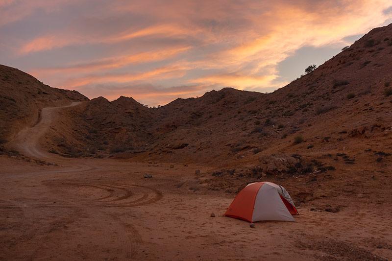 The tent set up at Bandar Al Khiran, the steep track visible behind below a fiery sunset sky.