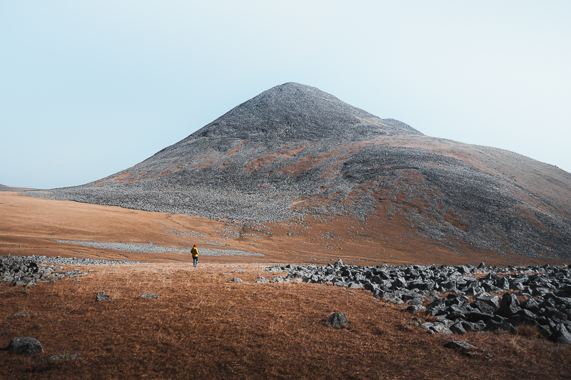 A person walks across the rolling grassy Javakheti Plateau beneath the scree covered slope of Shaori Mountain (Mount Koroghli)