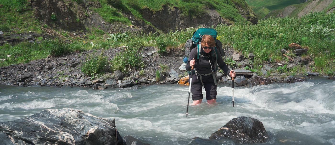 A hiker crossing the tributary of the Kvakhidistskali River between Atsunta Pass and Kvakhidi Meadows on the Shatili to Omalo trek in Georgia