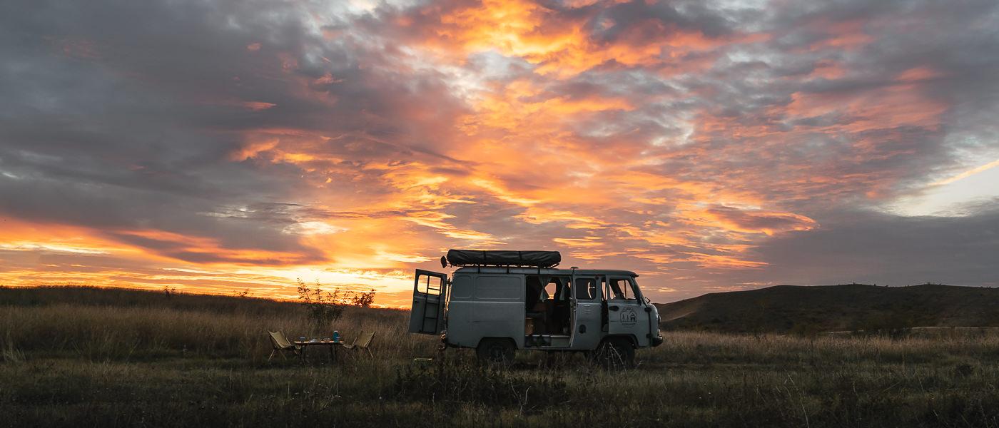 A fiery sunset sky above a UAZ Buhanka campervan near Shavi Mounatin in Vashlovani National Park