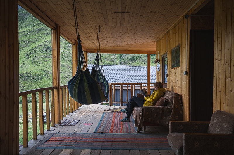 A person sits reading on the spacious wooden veranda upstairs at Shio's Stonehouse in Girevi