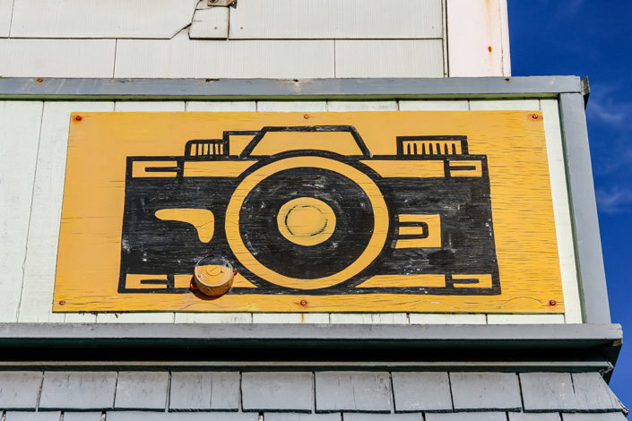 A photographic journey: A yellow and black camera icon on a shopfront sign, Fort Bragg, Mendocino County, California, USA