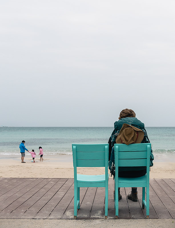 A woman wearing a hiking backpack sits on a green wooden chair looking out over a white sand beach to the sea