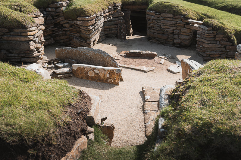 A central room with a main entrance connecting to a low passageway at the Skara Brae Neolithic historical site on Orkney Mainland