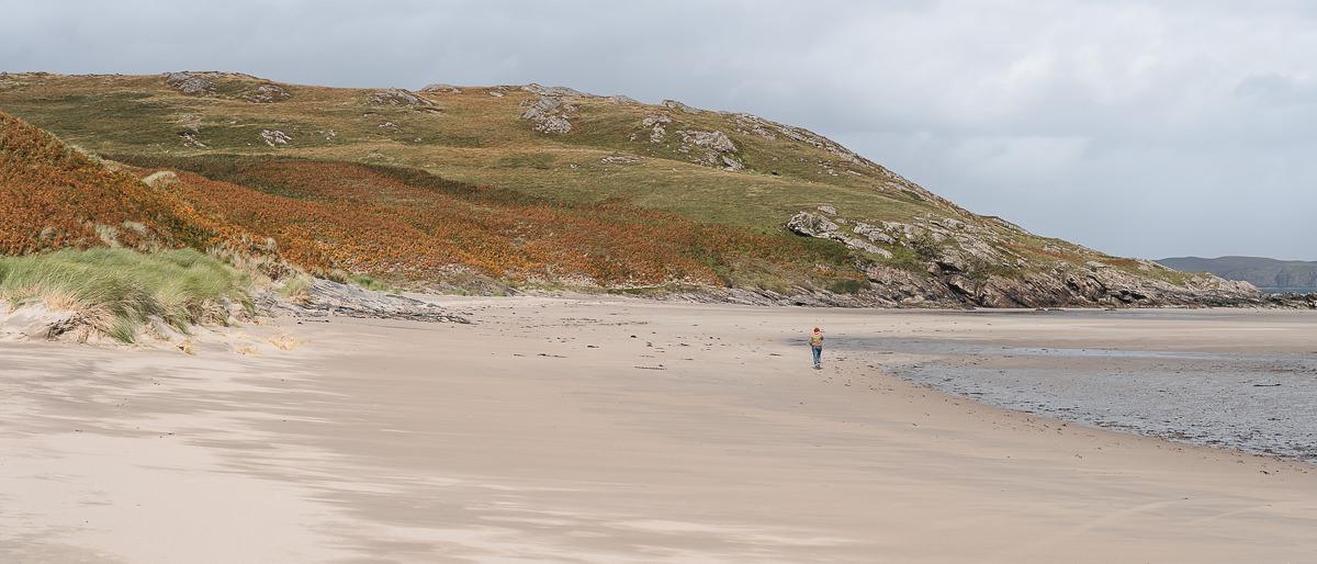 A person walks along sand at Skinnet Beach on Scotland's north coast