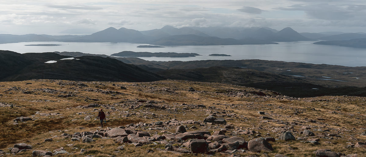 A person climbs the rocky and grassy hillside above the Bealach na Ba for a better view across to the Isle of Skye.