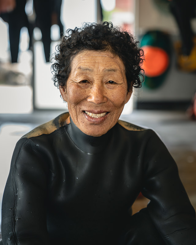 A smiling haenyeo in her wetsuit, kindly posing for a portrait shot