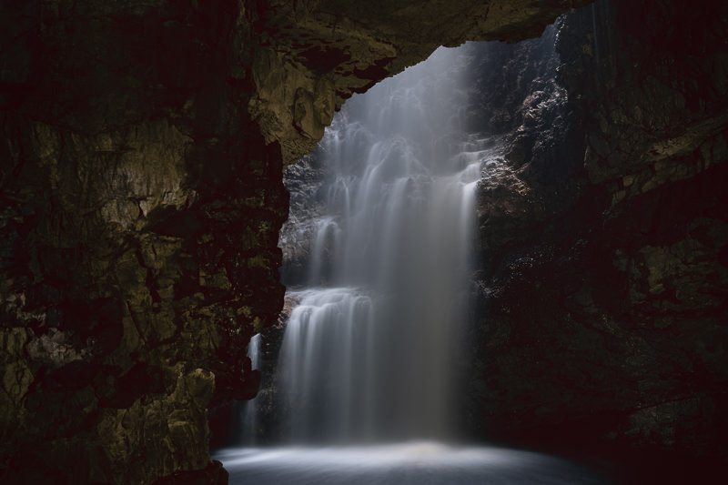 The waterfall rushing down from above in the inner chamber of Smoo Cave, one of the North Coast 500's must see sights.