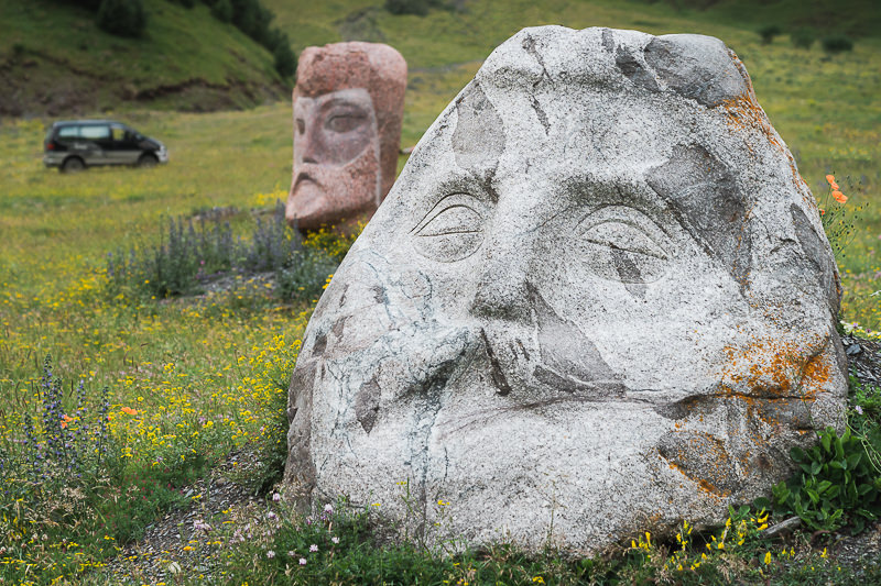 Giant heads carved out of stone sit on the grassy hillside near the village of Sno in Kazbegi, Georgia