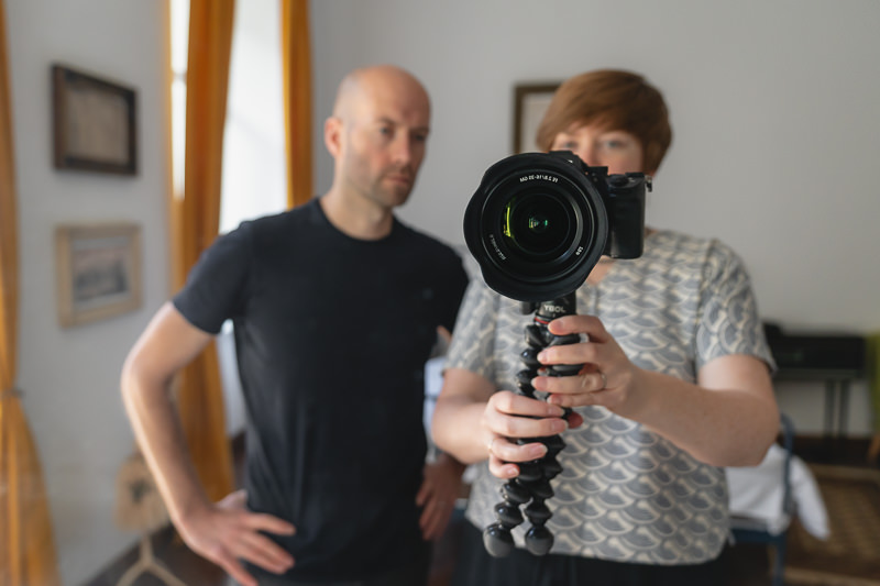 Displaying two items of our travel photography gear, the Sony A7III camera is mounted on the Joby 3K Gorillapod, reflected in the mirror of an apartment along with the person holding it