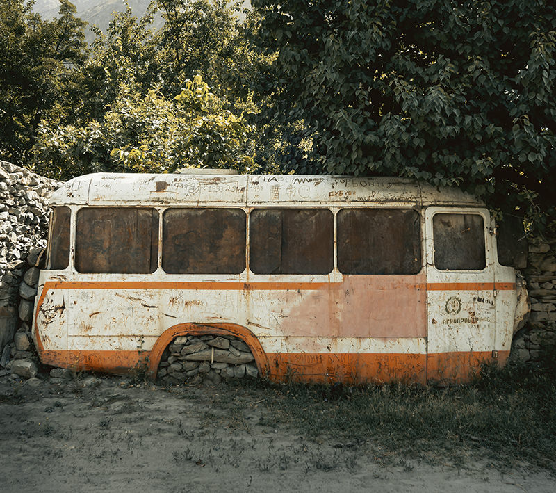 The shell of an old bus, now part of a village wall in the Western Pamirs of Tajikistan