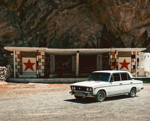 A Lada in front of Soviet bus stop with red stars and Marco Polo Sheep, on the Western Pamir Highway in Tajikistan